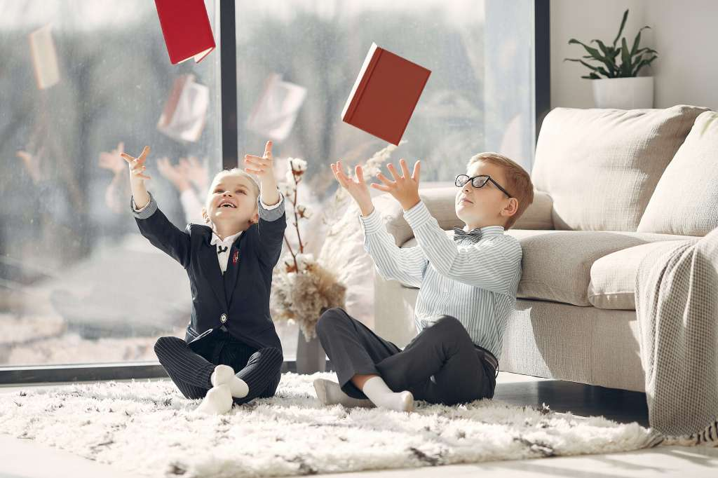 Cheerful kids celebrating victory in study room